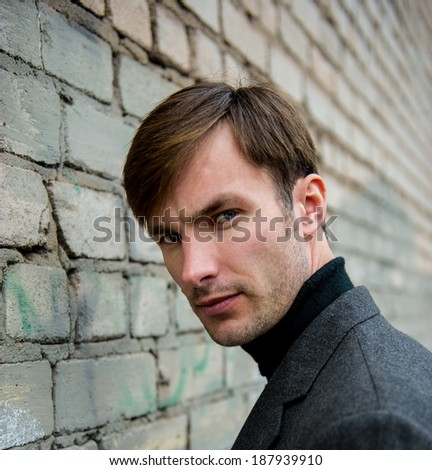 Portrait of a businessman who is focused and looking away against a brick wall, closeup  - stock photo