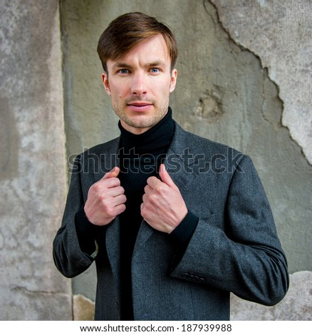 Portrait of a businessman who is focused and looking away against a  wall, closeup  - stock photo