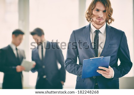 Portrait of a businessman with a clipboard concentrated at work on the foreground  - stock photo