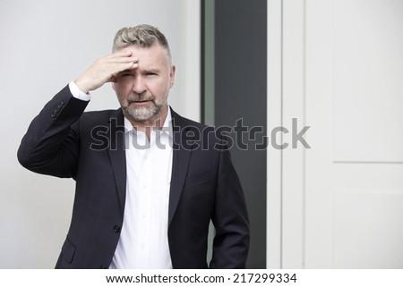 portrait of a businessman with a headache - stock photo