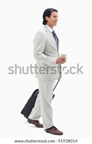 Portrait of a businessman with a takeaway coffee and a suitcase against a white background - stock photo