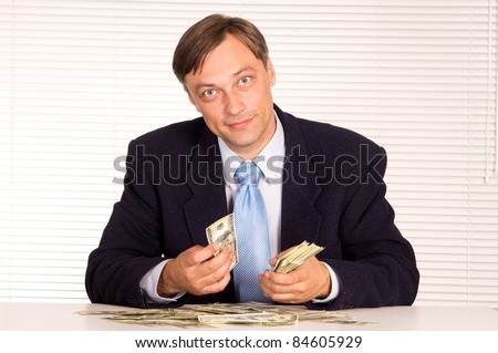 portrait of a businessman with cash at office