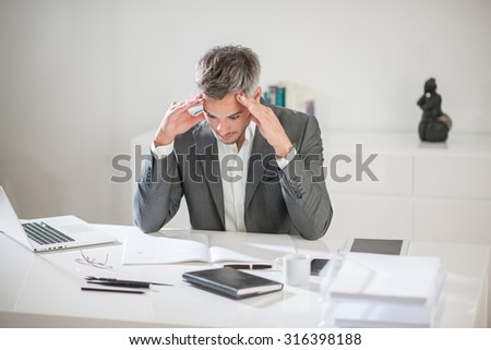 Portrait of a businessman with grey hair and beard having a hard time with some ideas. He is sitting at his white desk, holding his head in his hands above his notebook like if he was trying to think. - stock photo
