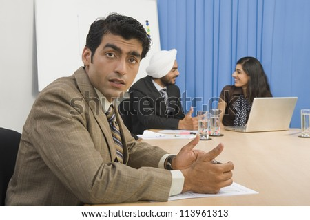 Portrait of a businessman with his colleague in a board room