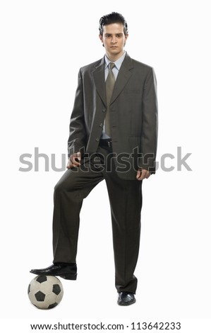 Portrait of a businessman with his foot on a soccer ball
