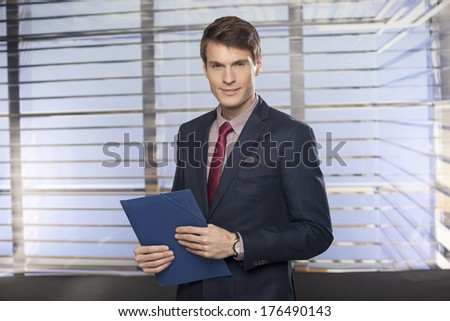 Portrait of a businessman with notepad or organizer in the office
