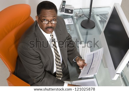 Portrait of a businessman with paperwork at computer desk - stock photo