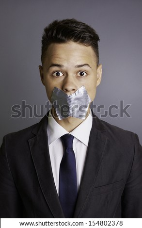 Portrait of a businessman with silver tape over his mouth, conceptual image, restriction, silence, frightens, eyes wide open, formal, isolated on gray background, studio shoot.