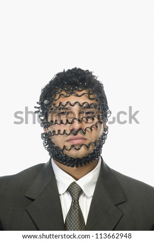 Portrait of a businessman wrapped with telephone cord - stock photo