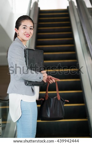 Portrait of a businesswoman going up escalator - stock photo