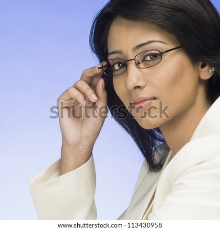 Portrait of a businesswoman holding her eyeglasses - stock photo