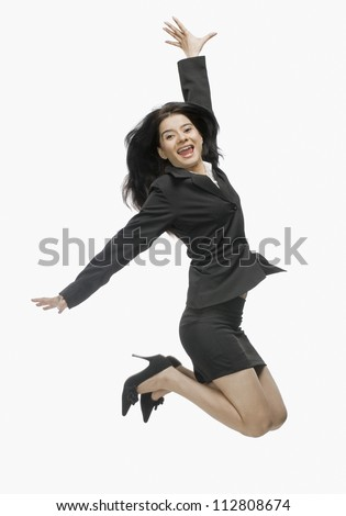 Portrait of a businesswoman jumping with joy - stock photo