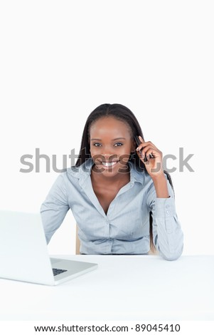 Portrait of a businesswoman making a phone call while using a notebook against a white background - stock photo
