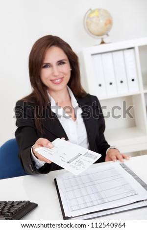 Portrait of a businesswoman offering secret envelop in office - stock photo