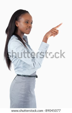 Portrait of a businesswoman pressing an invisible key against a white background - stock photo