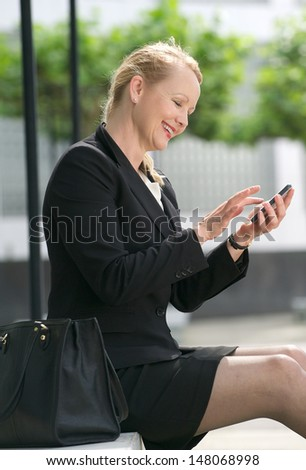 Portrait of a businesswoman sending message from mobile phone
