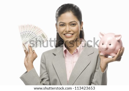 Portrait of a businesswoman showing Indian paper currency and a piggy bank