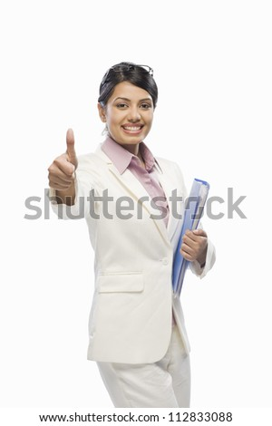 Portrait of a businesswoman showing thumbs up - stock photo