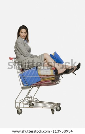 Portrait of a businesswoman sitting in a shopping cart