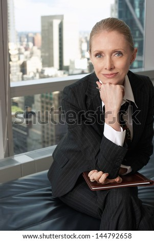 Portrait of a businesswoman sitting in office lobby - stock photo