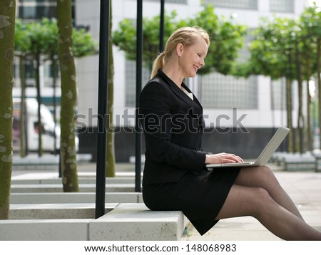Portrait of a businesswoman smiling with laptop outside