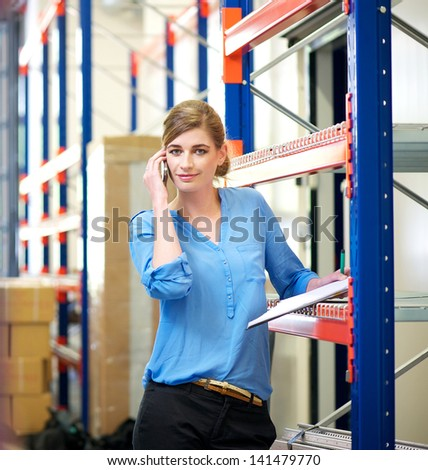 Portrait of a businesswoman talking on mobile phone in warehouse - stock photo