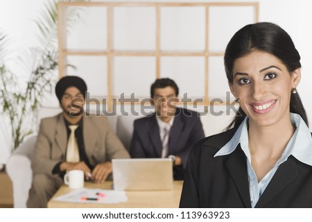 Portrait of a businesswoman with her colleagues in the background