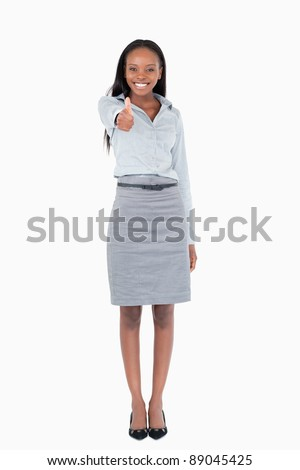 Portrait of a businesswoman with her thumb up against a white background - stock photo