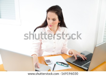 Portrait of a businesswoman with lots of work at office desk - stock photo