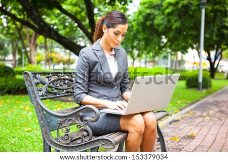 Portrait of a businesswoman working outdoors on laptop - stock photo