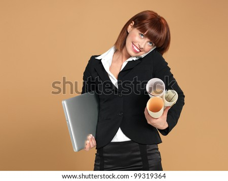 portrait of a bussy, young businesswoman, holding a laptop and some papers, talking on the telephone, on beige background - stock photo