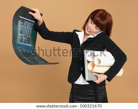 portrait of a bussy, young woman architect, holding a laptop and a blueprint, talking on the telephone, on beige background