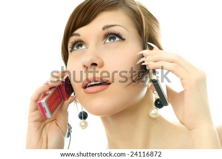 portrait of a busy beautiful young woman talking on two cell-phones