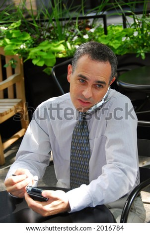 Portrait of a busy businessman in the city using pda and cell phone - stock photo