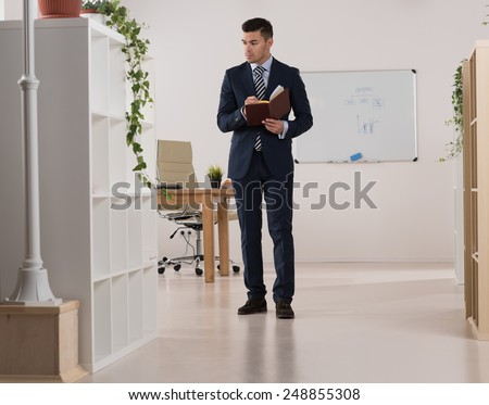 Portrait of a busy businessman taking notes and writing something in his organizer at his office - stock photo