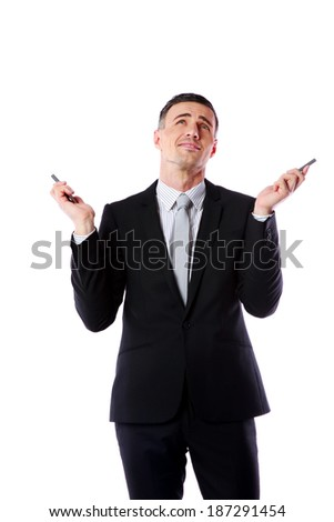 Portrait of a busy caucasian businessman holding two cell phones over white background