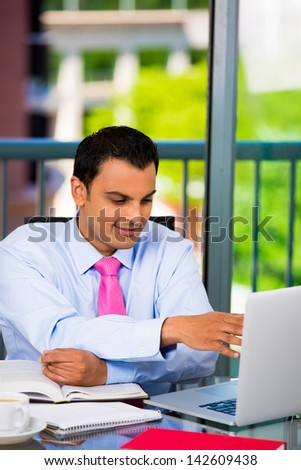 Portrait of a busy guy multitasking, taking notes, reading paper, surfing internet with laptop, isolated on a city background - stock photo