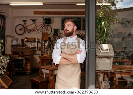 Portrait of a cafe owner standing in the doorway of his coffee shop. Young waiter standing with his arms crossed at the door of a restaurant and looking away. - stock photo