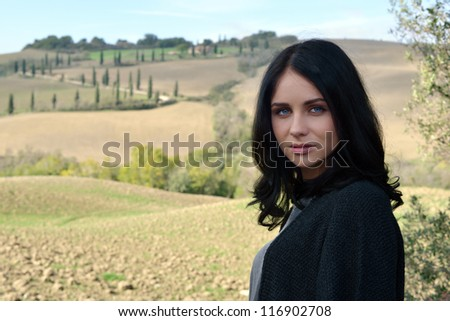 Portrait of a calm young woman with bright blue eyes on idyllic Tuscan landscape background. Italy - stock photo