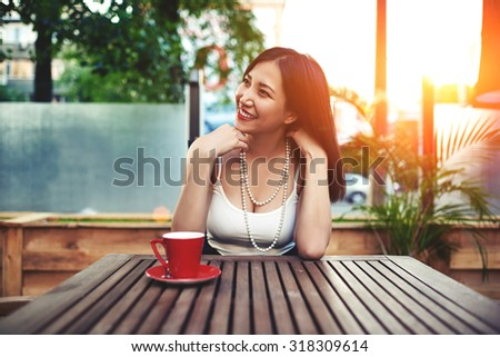 Portrait of a carefree young lady enjoying free time during summer vacation sitting in a modern cozy restaurant in exterior, cute woman feeling so happy smiling with amazing sunset on background - stock photo