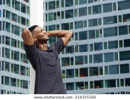 Portrait of a carefree young man standing next to building with hands behind head - stock photo