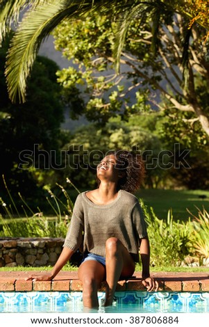 Portrait of a carefree young woman laughing next to pool - stock photo
