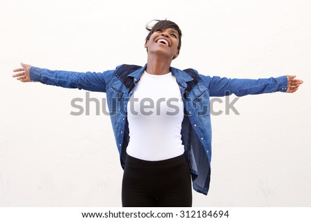 Portrait of a carefree young woman standing with arms spread open - stock photo