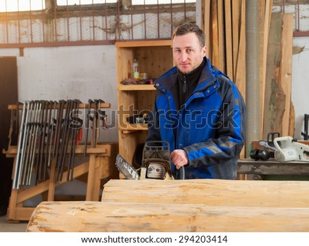 Portrait of a carpenter cutting trunk with chainsaw in his workshop - stock photo