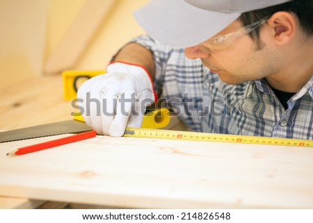 Portrait of a carpenter using a measuring tape - stock photo