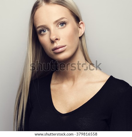 Portrait of a casual blonde woman in black top - stock photo