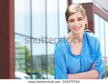 Portrait of a casual business woman relaxing outside of the office and smiling