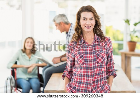 Portrait of a casual female artist with colleagues in the background at a bright office - stock photo