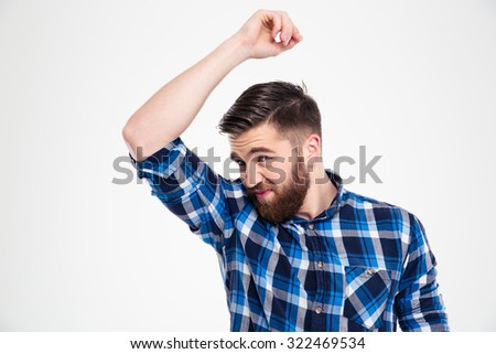 Portrait of a casual man smelling his armpit isolated on a white background - stock photo