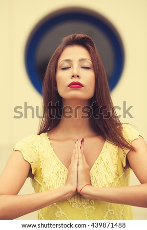 Portrait of a casual pretty woman meditating over nimbus symbol above head. Close up. Outdoor shot